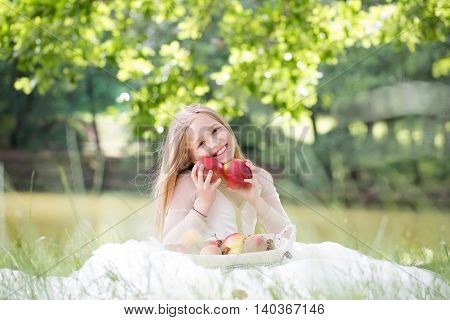 small girl kid with long blonde hair and pretty smiling happy face in prom princess white dress standing sunny day outdoor on natural background with fruit basket of red apples peach and cherry