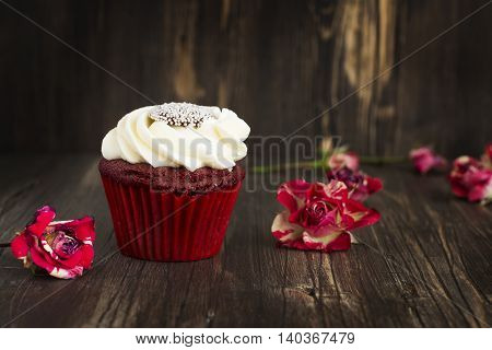 Red velvet cupcake and roses buds over grunge wooden background. Selective focus
