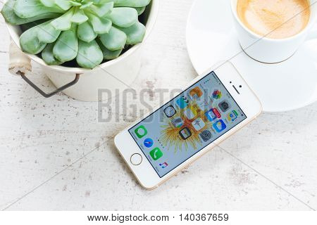 WARSAW, POLAND - JULY 17: New Iphone 5 SE in golden color with start page on screen with succulent and coffee