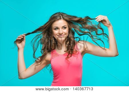 The young woman's portrait with happy emotions on blue background
