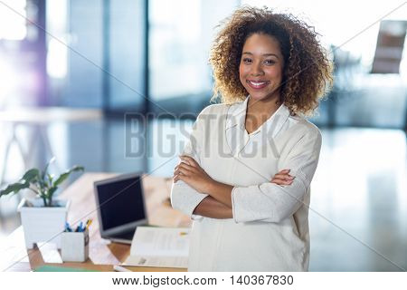 Portrait of smiling woman with arms crossed standing in office