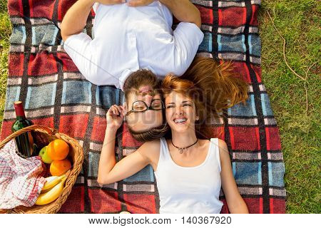 Top view of couple in love lying on a picnic blanket in the park with basket full of food and drinks placed next to them
