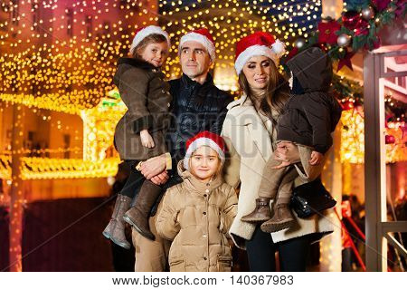 Big young family celebrating New Year and Christmas at the decorated Christmas fair