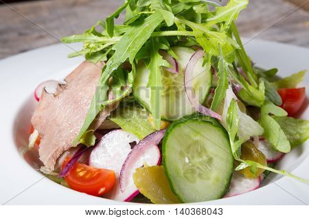 Prepared beef tongue served with mixed green vegetables salad