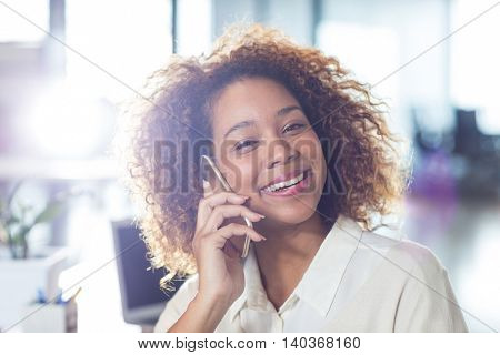 Portrait of smiling woman talking on mobile phone in office