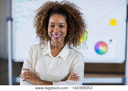 Portrait of smiling woman standing against whiteboard in office