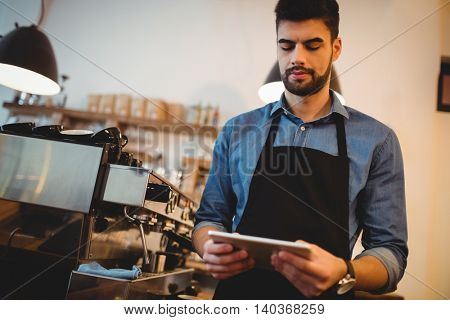 Young man using digital tablet at office cafeteria