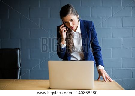 Young woman talking on phone while using laptop in creative office