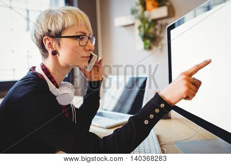 Female graphic designer discussing her work on mobile phone at office