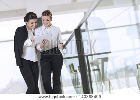 Two business colleagues standing in a modern office building hallway on a coffee break discussing work related matters