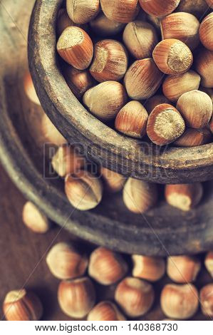 Hazelnuts in rustic round clay bowl on wooden background