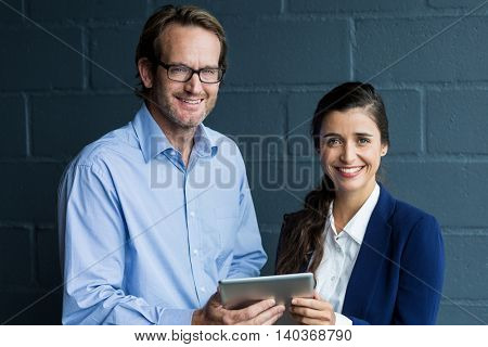 Portrait of smiling colleagues holding digital tablet against wall in office