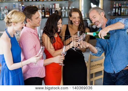 Man pouring champagne into glass in restaurant