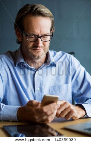 Businessman using mobile phone at desk in office