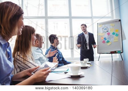 Smiling businessman giving presentation in front of coworkers in meeting room at creative office