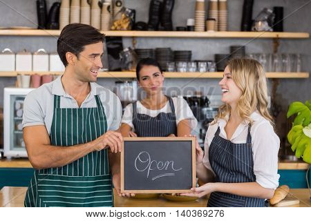 Smiling colleagues showing chalkboard with open sign in cafe