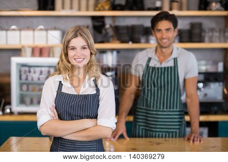 Portrait of smiling waitress standing with arms crossed in cafe