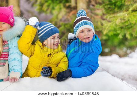 Little kids throw snowballs in the park hiding behind snow wall