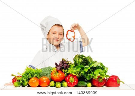 Kid boy playing chef cook preparing fresh salad holding slices of red pepper, isolated on white