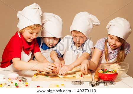 Four cute bakers, boys and girl in cook's uniform having fun making candy filled cookies