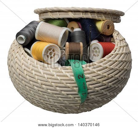 Wicker round box with accessories for needlework. Isolated on the white background no shadow.