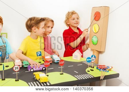 Smiling friends playing drivers with handmade cardboard light-signal, toy cars and road signs at the road playing field