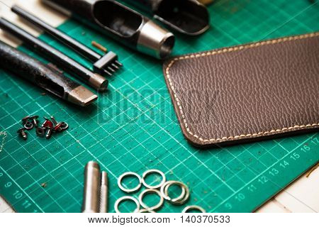 Genuine leather crafting tools make telephone case on green work table.