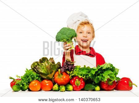 Smiling boy in cook's uniform holding fresh broccoli, isolated on white background