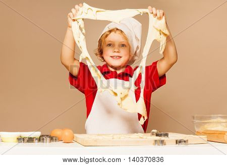 Young baker, boy in white apron and toque, looking through the big hole of dough, standing against the background with copy-space