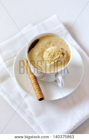 Cup of black coffee with ice cream and chocolate stick