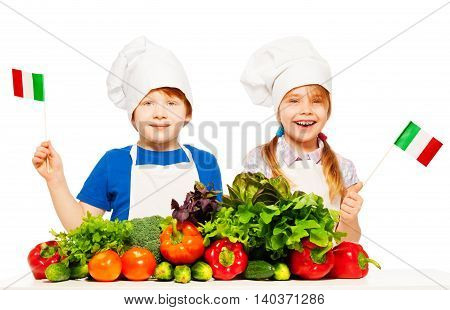 Two young Italian cooks, boy and girl in aprons and toques with green vegetables, waving flags of Italy, isolated on white