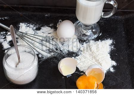 Ingredients for a cake on a black natural stone