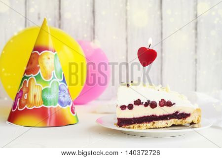 Piece of birthday cake over white background. Selective focus