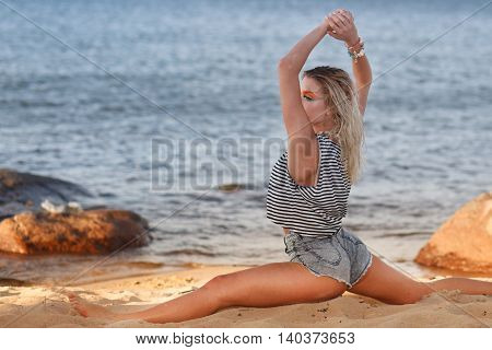 Young lady do exercises at the sea cost