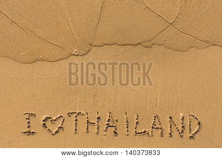 I love Thailand - text written on sandy beach with the soft wave.