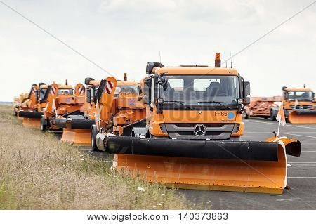 FRANKFURT GERMANY - JULY 24 2016: Orange Mercedes snow plough trucks waiting for winter at the Frankfurt International Airport