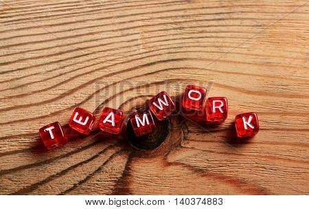 red dices with TEAMWORK word on wood