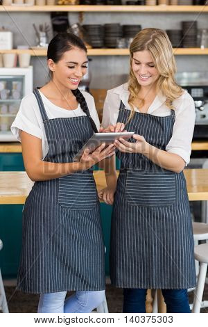 Smiling two waitresses using digital tablet at cafe