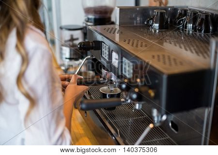 Mid section of waitress making cup of coffee at cafe