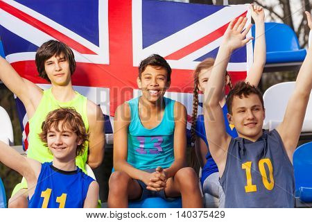 Happy British supporters, teenage multiethnic kids, sitting at the tribune with the flag of Great Britain