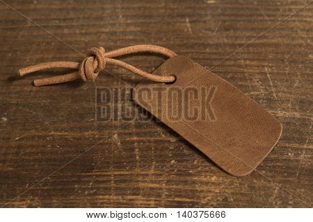 Grunge leather label on a wooden background