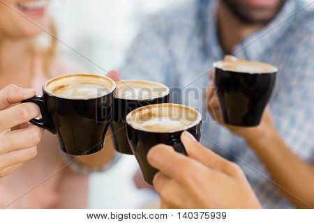 Group of happy friends toasting cup of coffee in cafe