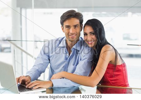 Portrait of smiling couple using laptop in cafe