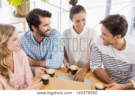Group of friends using laptop while having cup of coffee in cafe