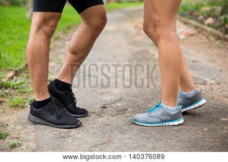 Couples feet standing on track in park