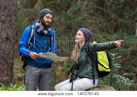 Hiker couple looking at map and pointing away at countryside