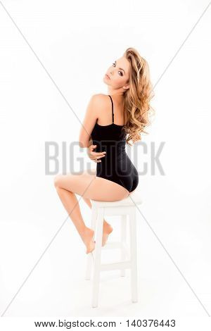 Beautiful Woman In Black Swimsuit With Shapely Back Sitting On Chair