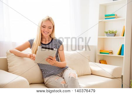 Happy Woman Sitting On Couch And Reading News On Tablet