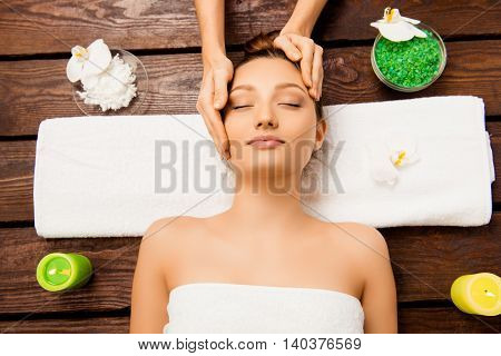 Relaxed young woman laying in spa salon with closed eyes and having massage