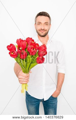 Portrait Of Handsome Boyfriend Holding Bouquet Of Red Tulips